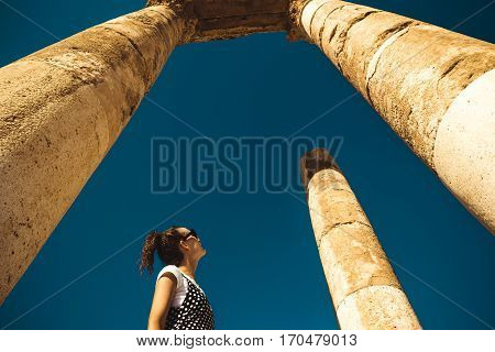 Photo of the Female tourist stand between columns exploring Hercules Temple remains on Amman Citadel hill. Ancient ruins. Travel concept. Tourist attraction. Woman looks up dreaming about adventure. Copy space.