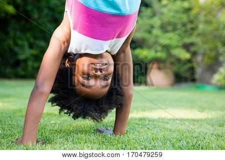 A kid doing a headstand in garden