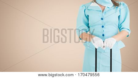 Mid section of air hostess holding luggage against beige background