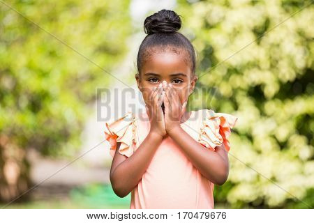 Little girl hiding her mouth at park on a sunny day
