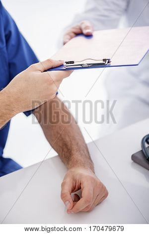 close up tablet which physician giving his colleague while bracing on desk in hospital