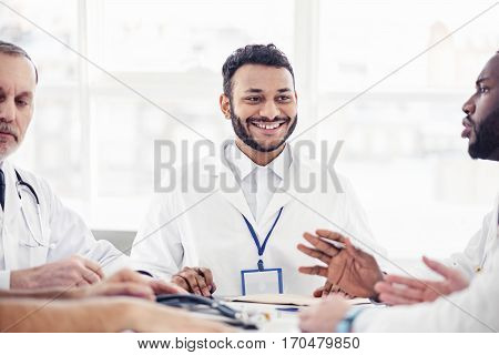 Cheerful bearded young asian doctor hearing arguments of his affiliates while sitting at table during conference in apartment of clinic