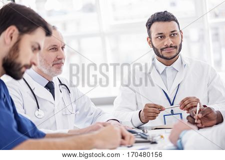 Calm young bearded therapeutic and smiling old caucasian physician listening their partner while sitting at conference in hospital room