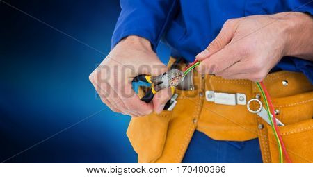 Mid section of handyman using pliers against blue background