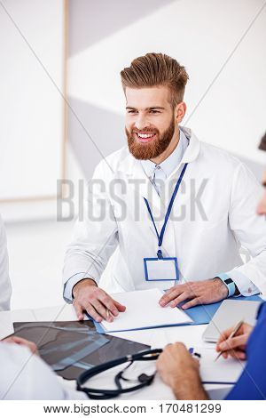 Outgoing medical adviser speaking with colleagues while leaning on table during conference in hospital apartment
