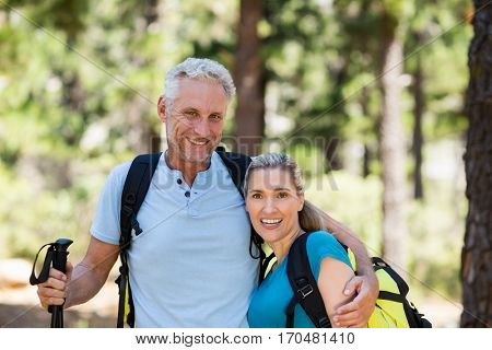 Portrait of couple smiling and holding arms on the wood