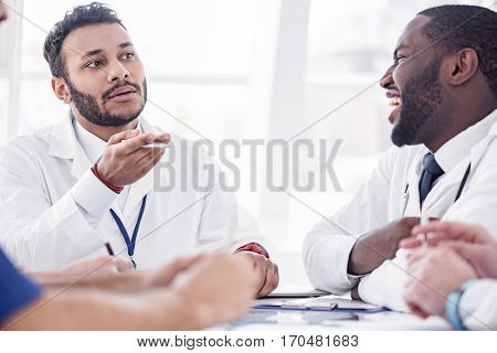 Calm bearded doctor telling with cheerful african therapeutic during conference in apartment of clinic
