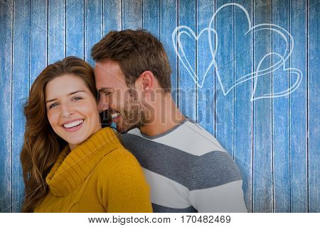 Close up of happy young couple embracing against wooden planks