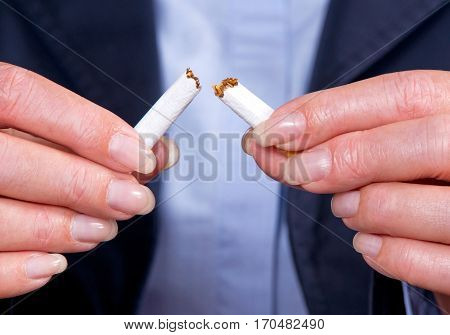 Quit smoking - female hands breaking cigarette