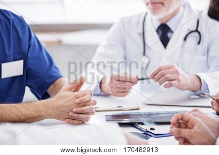 Focus on close up hands of doctor situating on table near x-ray at conference in office of clinic