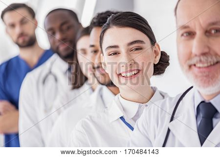 Focus on cheerful female medical adviser standing near her partners in hospital room
