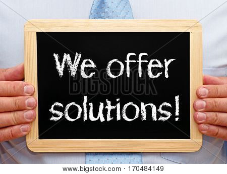 We offer solutions - Businessman holding chalkboard with text