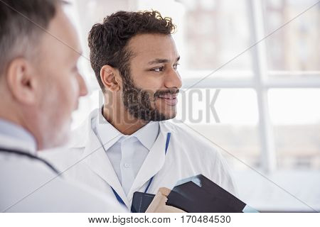 Outgoing medical adviser speaking with colleague at conference in clinic