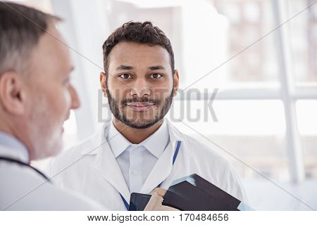 Focus on face of calm bearded doctor discussing with physician about x-ray of patient in hospital room
