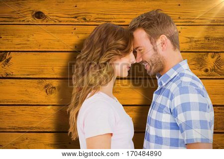 Happy young couple rubbing nose against yellow paint splashed surface