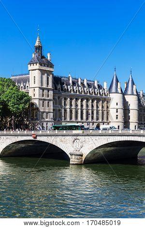 Bridge of Change (Pont au Change) over river Seine and Conciergerie Castle. Castle Conciergerie is a former prison located on west of the Cite Island and today it is a part of Palais de Justice. Paris France
