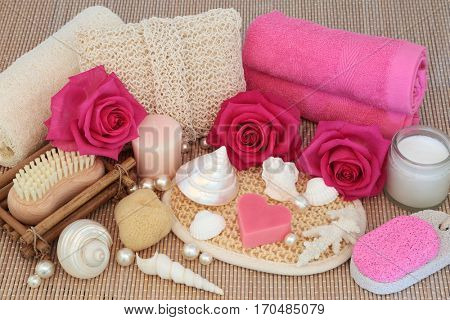Body scrub natural beauty products with pink rose flowers, pearls and shells over bamboo background.