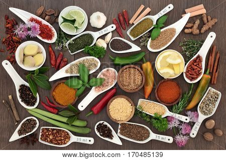 Spice and herb sampler with fresh and dried herbs and spices on oak background. High in antioxidants and vitamins.