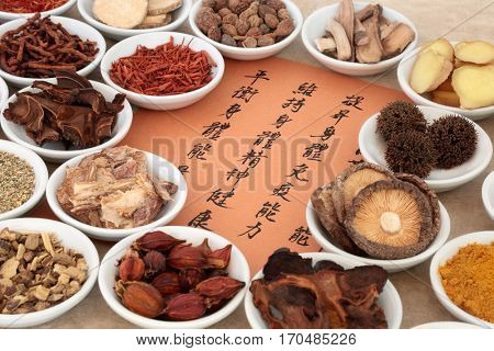 Traditional chinese herb selection used in herbal medicine in porcelain bowls with calligraphy script. Translation reads as  medicinal functions to maintain body and spirit health and balance energy.
