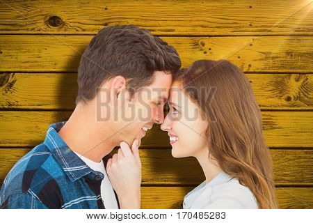 Couple with head against head and holding chin against green paint splashed surface