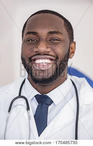 Portrait of cheerful bearded african physician locating in room of clinic during meeting
