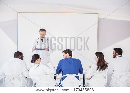 Cheerful young therapeutics speaking with each other at conference while sitting at table. Thoughtful mature doctor watching at x-ray while standing near white board