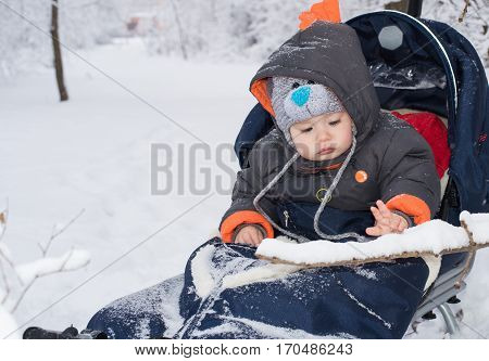 A child plays with snow on his sledge. Child sledding. Toddler kid riding sledge. Children play outdoors in snow. Kids sled in snowy park. Outdoor winter fun for family Christmas vacation.