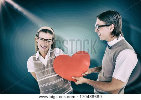 Geeky hipster offering red heart to his girlfriend against blue vignette background