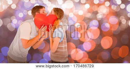Geeky hipster couple kissing behind heart card against glowing background