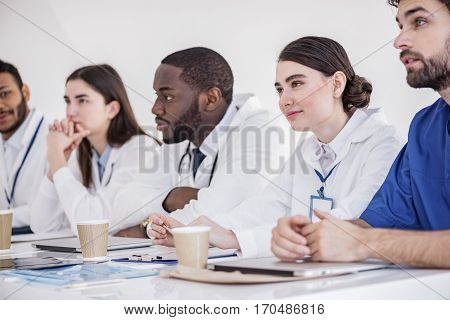 Cheerful therapeutics hearing talk while sitting at table during meeting in white office of clinic