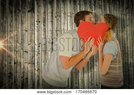 Geeky hipster couple kissing behind heart card against digitally generated grey wooden planks