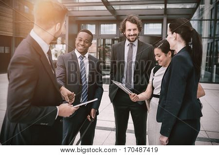 Group of cheerful businesspeople having conversation in office premises