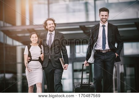 Businesswoman with colleagues walking in office premises