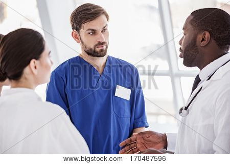 Calm team of doctors speaking with each other while standing in room of hospital at conference