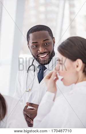 Focus on outgoing bearded male medical adviser speaking with female physician during break at conference in office of clinic
