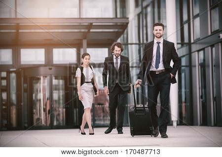 Businesspeople with colleagues walking in office premises
