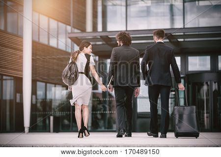 Rear view of businesswoman with colleagues walking in office premises