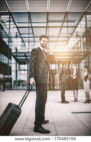 Businessman holding suitcase talking on mobile phone in office premises