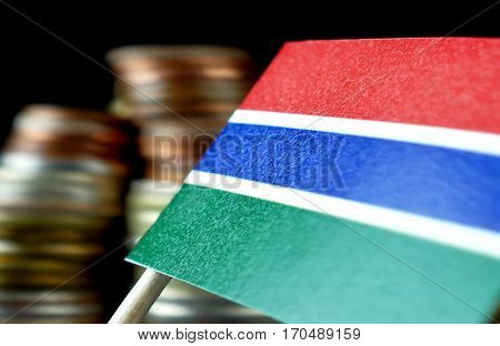 Gambian Flag Waving With Stack Of Money Coins Macro