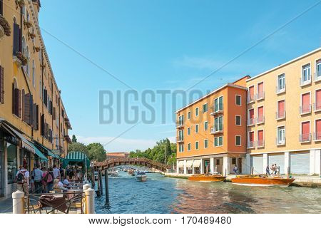 VENICE,ITALY-March 26, 2016.Tourists on water street with Gondola in Venice on May 26,2016. its entirety is listed as a World Heritage Site, along with its lagoon.May 26 VENICE,ITALY
