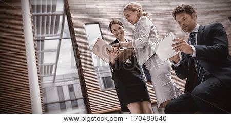 Businesspeople using laptop and tablet in office premises