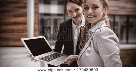 Portrait of businesswomen using laptop and digital tablet in office premises