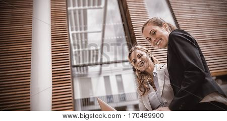 Portrait of businesswomen sitting with laptop in office premises