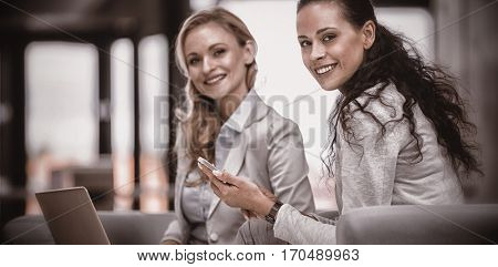 Portrait of smiling businesswomen holding smart phone and laptop in office