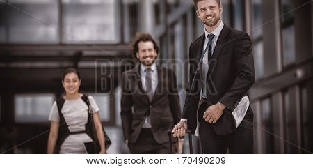Smiling businesswoman with colleagues walking in office premises