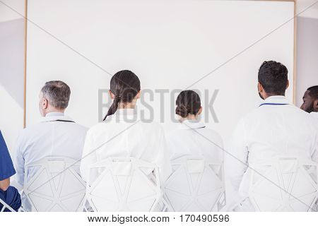Medical advisers sitting at table opposite white board during meeting in apartment of clinic