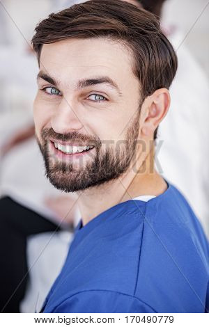 Portrait of smiling handsome bearded medical adviser situating during meeting in apartment of clinic