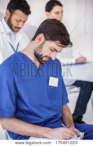 Outgoing physician noting during meeting while sitting near his colleagues in apartment of hospital