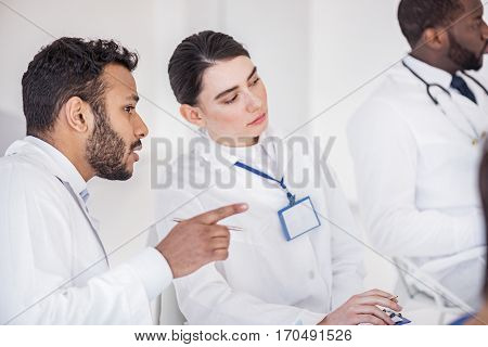 Considerate bearded male physician telling with serene female medical adviser while gesturing his hands and sitting on seat near her at conference in hospital apartment
