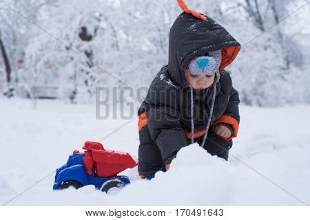 A child plays a toy truck in the snow. Shovel snow truck.Children's toy cars. Car Models. Kids toys. The child is played by an car. Little boy playing with snow spade and truck.